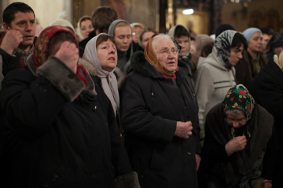 Moscow, Russia, 06/01/2011..Russian Christians cross themselves as they attend an Orthodox Christmas service at Peter Paul church in central Moscow, late on Christmas Eve. Christmas falls on January 7 for Orthodox believers in the Holy Land, Russia and other Orthodox churches that use the old Julian calendar instead of the16th-century Gregorian calendar.