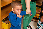 Education preschool first days of school 2-3 year olds separation sad boy holding teacher's hand.