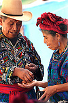 An old couple in traditional dress handing changes to each other in Sololá's Market day. Sololá. Guatemala