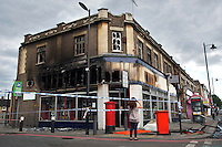 A young woman takes a photograph of a burnt out shop and building where rioting took place two nights earlier in Tottenham, London borough of Haringey. London saw the beginnings of riots on Saturday evening, after a peaceful protest in response to the shooting by police of Mark Duggan during an attempted arrest, escalated into violence. By the third night of violence, rioting had spread to many areas of the capital and to other cities around the country.