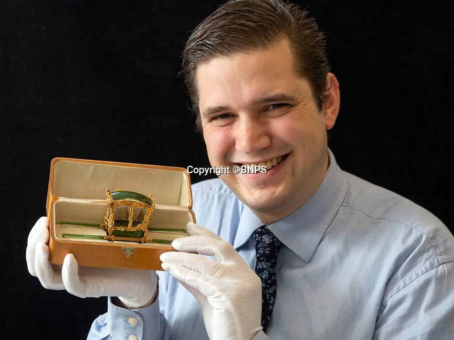 BNPS.co.uk (01202 558833)<br /> Pic: PhilYeomans/BNPS<br /> <br /> Piers Critchlow from the Cotswold Auction Co carefully hold the Russian gem...<br /> <br /> In from the cold - £500,000 Romanov treasure is hot property at Cotswold auction.<br /> <br /> An exquisite Faberge antique believed to have been made for the Russian Royal family over 100 years ago sold yesterday for a whopping £500,000...over 5 times it's estimate.<br /> <br /> The model of a sedan chair by the iconic Russian jewellers was one of the state treasures seized and sold off by the communist regime following the Russian Revolution.<br /> <br /> It was first sold at high-end Anglo-Russia antique dealers Wartski in London in 1929, where it was bought by a K.W Woollcombe-Boyce for only £75.<br /> <br /> The ornate item, crafted from Jadeite, gold, rock crystal and mother of pearl, has remained in the family ever since and is now being sold by a direct descendant of Mr Woollcombe-Boyce.<br /> <br /> Experts from the Cotswold Auction Company gave the small Russian antique a pre-sale estimate of only £100,000, but always anticipated it could go for much more than that.