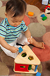 12 month old baby boy sitting playing with shape sorter  block held in pincer grip vertical