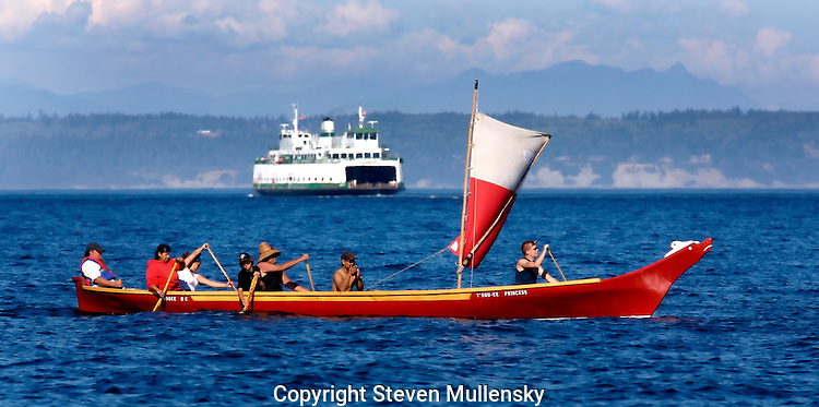 """Paddlers from Turtle Island in British Columbia paddle their canoe along Admiralty Inlet at the mouth of Port Townsend Bay in the State of Washington. The paddlers were on their way to join other tribes in the annual Puget Sound """"Traveling the traditional highways of our Ancestors"""" paddle to Lummi Island."""