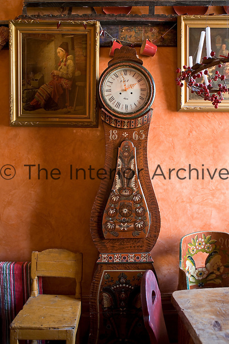 A hand-painted Swedish Mora clock stands against a distressed orange wall in the kitchen