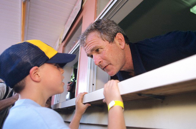 04 Jul 1999, New Hampshire, USA --- Republican presidential candidate George W Bush takes a food order from a child at an ice cream stand on July 4th in New Hampshire.   Location: Amherst, NH.  --- Image by © Brooks Kraft/Corbis