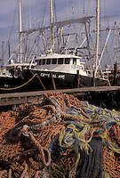 AJ3288, fishing boats, nets, Cape May, New Jersey, Fishing nets are piled on a dock while fishing boats are docked in the harbor along the Atlantic Coast in Cape May in the state of New Jersey.