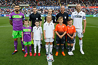 Mike van der Hoorn of Swansea City (R), Marlon Pack of Bristol City (L) and referee Gavin Ward with assistants pose with children mascots during the Sky Bet Championship match between Swansea City and Bristol City at the Liberty Stadium, Swansea, Wales, UK. Saturday 25 August 2018