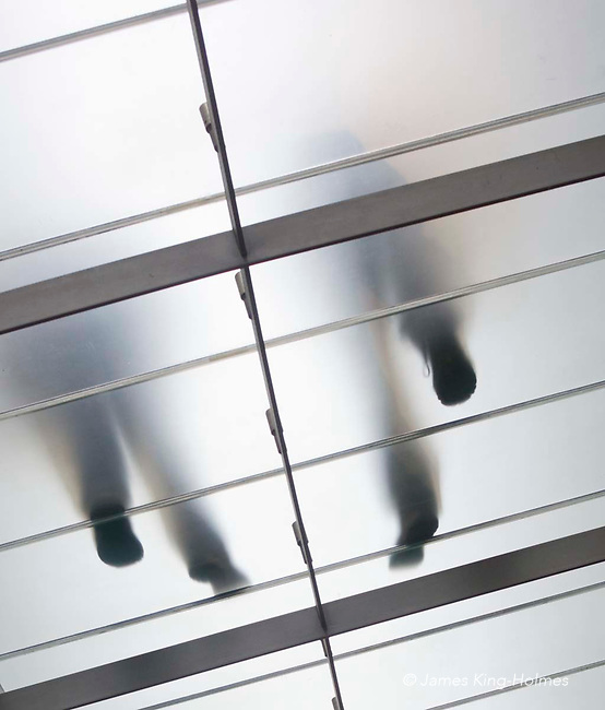 View from underneath a frosted glass walkway of pedestrians walking above. View from underneath a frosted glass walkway of pedestrians walking above.