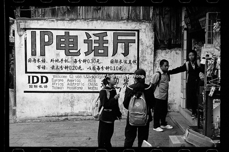 Students stand outside a telephone shop in the ancient city of Dali, Yunnan province, China, October 2013.