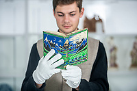 BNPS.co.uk (01202 558833)<br /> Pic: MaxWillcock/BNPS<br /> <br /> Pictured: Specialist Senan MacDonagh with the first-impression copy of The Hobbit, in the saleroom at Duke's in Dorchester, Dorset.<br /> <br /> A rare first impression edition of Tolkien's classic children's book The Hobbit has sold for a whopping £59,800.<br /> <br /> The sought-after copy was one of the first ever printed and includes original maps and illustrations by the author.<br /> <br /> It is adorned with a wraparound cloth depicting the iconic dark blue mountains and deep-green forests of Tolkien's fantasy world.<br /> <br /> The family who sold it were completely unaware of its true worth until a valuer visited their home in Dorset and spotted it on a dusty bookshelf.