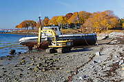 Boat washed up on shore in Rockland Harbor, near the Rockland Breakwater in Rockland, Maine USA.