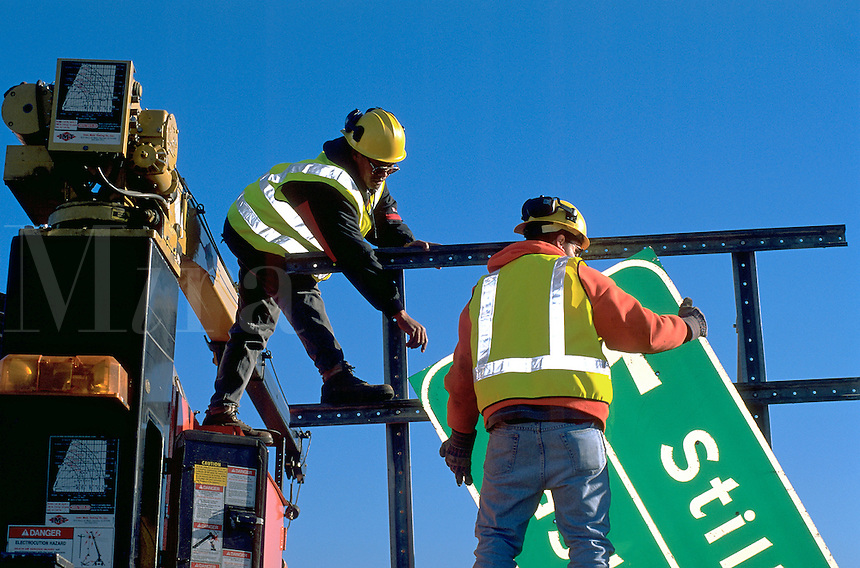 Construction workers at work installing a freeway sign.