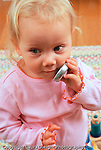18 month old toddler girl pretend play talking on cell phone vertical Caucasian