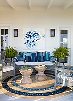 In the porch the wicker furniture is painted the same hue of blue, creating a sense of unity while contrast is provided by mixing in furniture made from varying materials and finishes. A pair of smooth Indonesian teak side tables play off the more textural painted wicker.