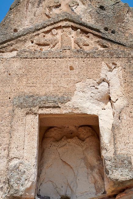 close up of the facade and relief sculptures of the Phrygian temple of Aslankaya, 7th century BC. Phyrigian Valley, Emre Lake, near Doger, Turkey.<br /> <br /> On the triangular roof over the facade are two sphinxes (winged figures with the head of a human and the body of a lion), facing one another, take place. In the main facade, below, the sphinxes in a niche, a cult statue of Kybele or the Great Mother (vandalised and destroyed) was flanked by two lions. This main facade is ornamented with relief geometrical patterns.