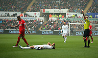 Nathaniel Clyne of Liverpool (L) sees a yellow card by match referee Roger East for his foul on Jefferson Montero of Swansea City who is on the ground during the Barclays Premier League match between Swansea City and Liverpool at the Liberty Stadium, Swansea on Sunday May 1st 2016