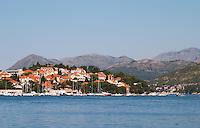 Pleasure boats moored on buoys and along the key, villas along the coast. Mountains mountain tops in the background. Luka Gruz harbour. Babin Kuk peninsula. Dubrovnik, new city. Dalmatian Coast, Croatia, Europe.