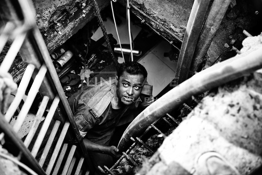 A rescue worker trying to go inside of the collapsed building – Rana plaza, in Savar, near Dhaka, Bangladesh.