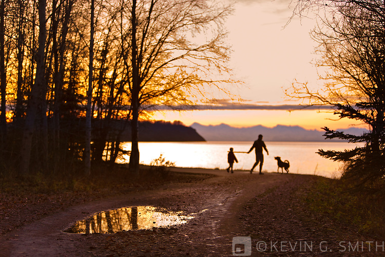 People enjoying the Tony Knowles Coastal Trail at sunset, silhouettes, view looking East towards Point Woronzof and the Alaska Range, Anchorage, Southcentral Alaska, USA. Not Model Released