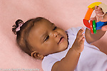 5 month old baby girl closeup on back holding colorful wooden ring toy with rings that slide around it reaching to touch with one had as she holds it