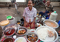 Myanmar, Burma, Yangon.  Street Food Vendor.  Noodles, boiled eggs, spicy sausages, pork, cabbage, and soup are among the treats she has to offer.  The lady is wearing a light coating of thanaka paste on her cheeks, as a cosmetic sunscreen.