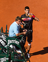 25-05-11, Tennis, France, Paris, Roland Garros,    Novak Djokovic drinking during changeover, in the chair umpire Cedric Mourier