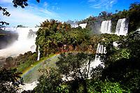 Beautiful Iguazu Falls cataracts, with a lush, green rainforest foreground<br /> and a rainbow across the rapids, in Iguacu National Park, Iguazu Brazil