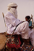 In-Gall, near Agadez, Niger - Tuareg on his Camel at Annual Cure Salé, Annual Gathering of Tuareg Nomads.  As is their custom, this man covers his mouth with the tagulmust, the Tuareg veil.  A distracting camel's nose has been digitally removed from the area immediately behind the rider's back.