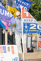 Samson Racioppi, organizer for the alt-right organization Super Happy Fun America, sets up pro-Trump flags and the stage as the group demonstrates against facemasks, vaccines, and pandemic closures, and in support of the reelection of President Donald J. Trump near the residence of Massachusetts governor Charlie Baker in Swampscott, Massachusetts, on Sat., Sept. 26, 2020. Super Happy Fun America is most well known for organizing the Straight Pride Parade in Boston on August 31, 2019.
