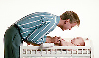 Time for change 4 Father plays with baby as he changes diaper. Father & baby. Douglaston NY.