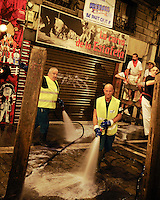 Cleaning workers clean Estafeta street before the fourth run of the bulls of the San Fermin festival, on July 10, 2012, in the Northern Spanish city of Pamplona. The festival is a symbol of Spanish culture that attracts thousands of tourists to watch the bull runs despite heavy condemnation from animal rights groups. (c) Pedro ARMESTRE