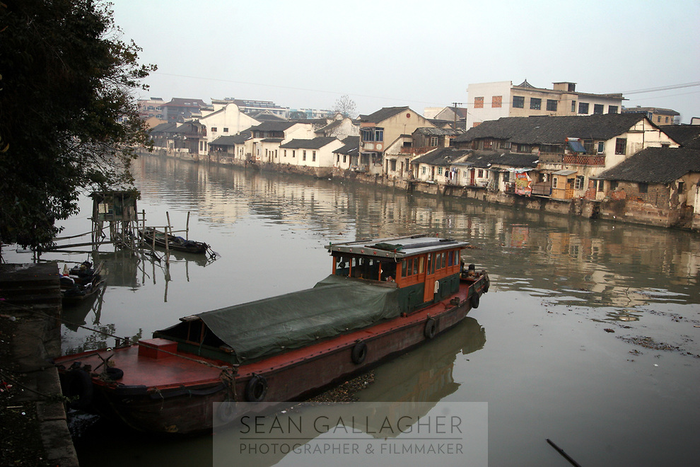 CHINA.Wuzhen. The town of Wuzhen is located in the center of the six ancient towns south of Yangtze River, 10 miles north of the city of Tongxiang, Wuzhen displays a two-thousand-year history in its ancient stone bridges, stone pathways between the mottled walls and its delicate wood carvings all lying above a network of canals and small lakes. 2008