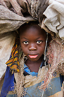 0095<br /> Sierra Leone, Africa. Young ragpicker carrying bags on his head as he works.
