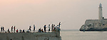 04/11/2004:  Journal photo by Ted Richardson:  Fishermen test the waters at sunset in Havana Bay across from the lighthouse of the Castillo del Morro, a Spanish fortress built in the late 16th Century..