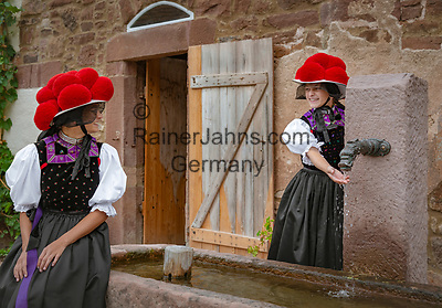 Deutschland, Baden-Wuerttemberg, Ortenaukreis, Gutach: Schwarzwaelder Freilichtmuseum Vogtsbauernhof - zwei junge Frauen in Schwarzwaelder Tracht mit rotem Bollenhut am Brunnen vor dem Schloessle von Effringen | Germany, Baden-Wurttemberg, Gutach: Black Forest Open Air Museum Vogtsbauernhof - two young women in Black Forest costume with red Bollenhat sitting in front of Effringen castle