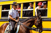 Police man on a horse by a yellow school bus in Washington DC, USA