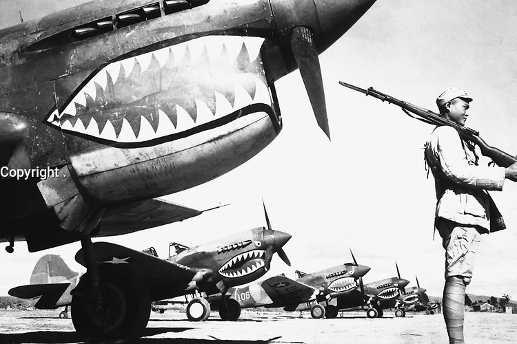 """A Chinese soldier guards a line of American P-40 fighter planes, painted with the shark-face emblem of the """"Flying Tigers,"""" at a flying field somewhere in China.  The American pursuit planes have a 12-to-1 victory ratio over the Japanese.  Ca. 1942.  (OWI)<br /> Exact Date Shot Unknown<br /> NARA FILE #:  208-AA-12X-21<br /> WAR & CONFLICT BOOK #:  1149"""