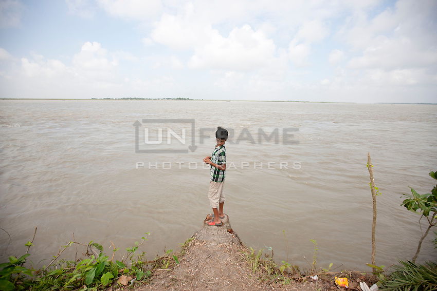 A child stand on the bank of river Padma. Every year in Bangladesh, millions of people are affected by river erosion that destroys home, farmland, communication infrastructure. In the last couple of days erosion by the Padma River has caused extensive damages to houses, agricultural lands, roads etc. In Dohar, lots of people lost their lands and homes due to Padma river banks erosion. Dohar, Dhaka, Bangladesh.