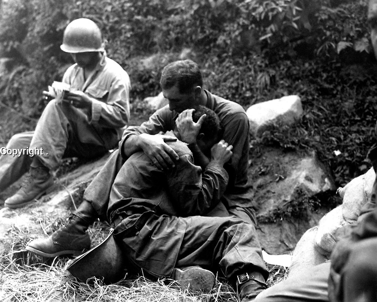 A grief stricken American infantryman whose buddy has been killed in action is comforted by another soldier. In the background a corpsman methodically fills out casualty tags, Haktong-ni area, Korea.  August 28, 1950.  Sfc. Al Chang. (Army)<br /> NARA FILE #  080-SC-347803<br /> WAR & CONFLICT BOOK #:  1459