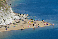 BNPS.co.uk (01202 558833)<br /> Pic: Graham Hunt/BNPS<br /> <br /> What a difference a year makes..<br /> <br /> The windswept beach at Durdle Door in Dorset is virtually deserted today, exactly a year after glorious weather saw thousands flock to the iconic landmark. <br /> <br /> A few stragglers, wrapped up in hats and coats, braved the wind and rain to walk along the beach that became a magnet for sunseekers during last year's pandemic.<br /> <br /> Whilst last year saw temperatures into the mid-20s - way above the average for May - today the thermometer struggled to reach 10C.<br /> <br /> (This picture was taken on 20/5/20)