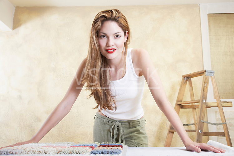 Portrait of young woman with carpet samples
