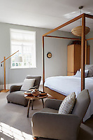 A pair of grey armchairs are place either side of a contemporary wooden four-poster made by Mark Tuckey in the master bedroom