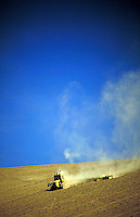 tractor ploughing bare field. Dust cloud formed behind. erosion, plough, wind, dirt, agriculture, farming. Oregon USA.