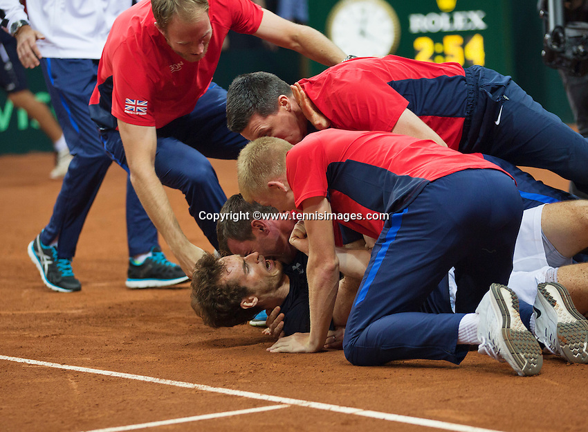 Gent, Belgium, November 29, 2015, Davis Cup Final, Belgium-Great Britain, day three, Andy Murray (GBR) goes down on the clay after defeating David Goffin and scoring the winning point for Great Britain 3-1, captain Leon Smith and his team members embrace him, Great Britain wins the Davis Cup 2015.<br /> Photo: Tennisimages/Henk Koster