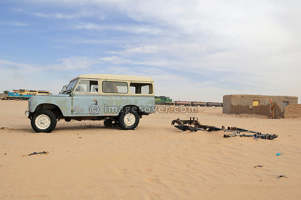 Africa, Mauritania, Sahara Desert. Famous mauritanian iron ore train passing by behind an old Series 3 Land Rover Santana and a Land Rover chassis buried in the sand at a small village along the railroad track from Nouadhibou to Choum. --- No releases available. Automotive trademarks are the property of the trademark holder, authorization may be needed for some uses.