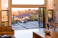 Evening light into Margarido House, Oakland, California - LEED. Sliding glass doors opening living room to patio overlooking San Francisco Bay