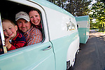 Family sitting in the front seat of a two-toned sea foam green and antique white 1955 Dodge C-3 Town Panel vehicle. The Dodge is towing a 1954 Zollinger VA-KA-SHUN-ETTE vintage travel trailer canned ham (same two-toned color).