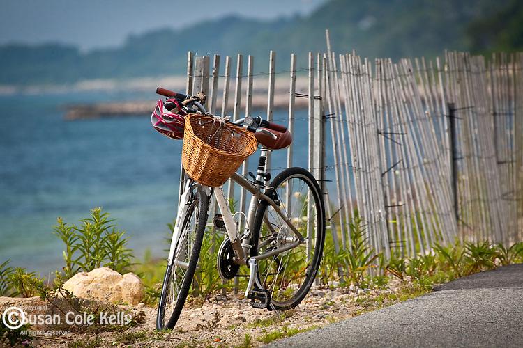 A bike with a wicker basket waits for its owner on the Shining Sea Bike Path, Falmouth, Cape Cod, MA, USA