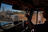 Truck driver Nick Atkins behind the wheel, waves to a passing truck on the Gibb River Road, on his way from Kununurra to Kalumburu.