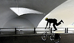 The indefatigueable John Allison, a Pittsburgh Post-Gazette editor and my colleague there, who commutes by bicycle from the north shore daily shows off while wearing business attire during his commute as he passes through the tunnel in Point State Park. The reflecting pool splashes a wedge of light onto the ceiling. <br /> copyright JimMendenhallPhotos.com 2013